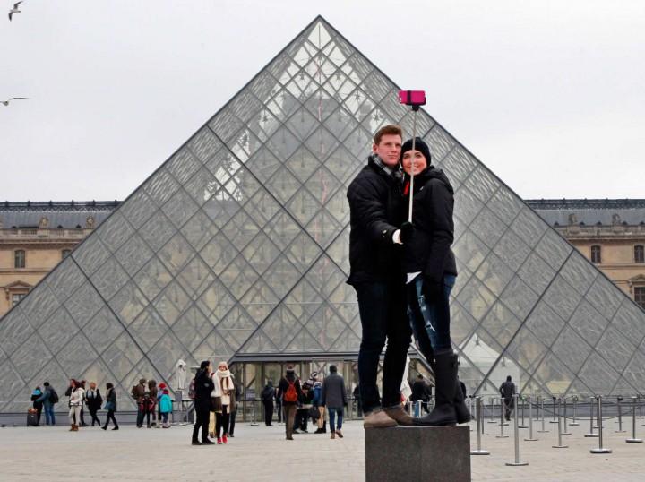 Pareja tomando un autorretrato. Al fondo, la entrada al Museo de Louvre en París, Francia.