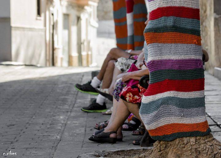 Hilando vidas. Personas disfrutando de Hilando Vidas, exposición de arte urbano realizado por las Amas de Casa de Alcublas.